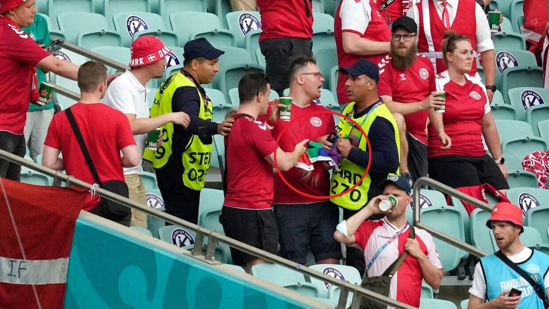 En steward på stadion i Baku ser ud til at konfiskere et regnbueflag fra danske fans.