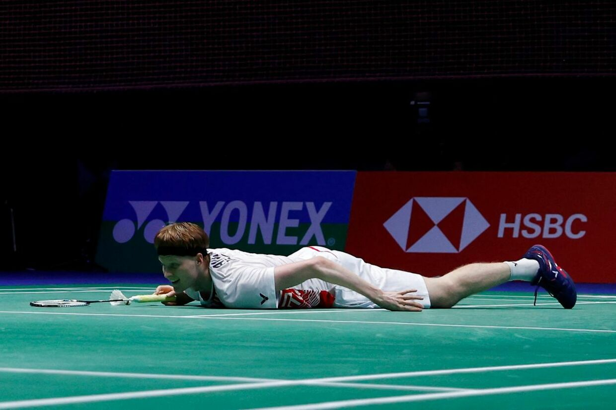 Denmark's Anders Antonsen lies on the court after falling during a point against Denmark's Viktor Axelsen during their men's singles semi-final match on day four of the All England Open Badminton Championship at the Utilita Arena in Birmingham, central England, on March 20, 2021. (Photo by Adrian DENNIS / AFP)