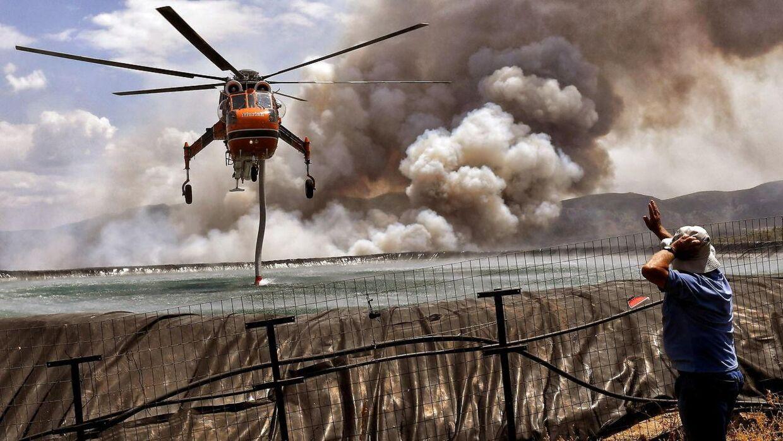 En helikoptor super vand op fra havet, for at sprøjte det ud over skovbranden.