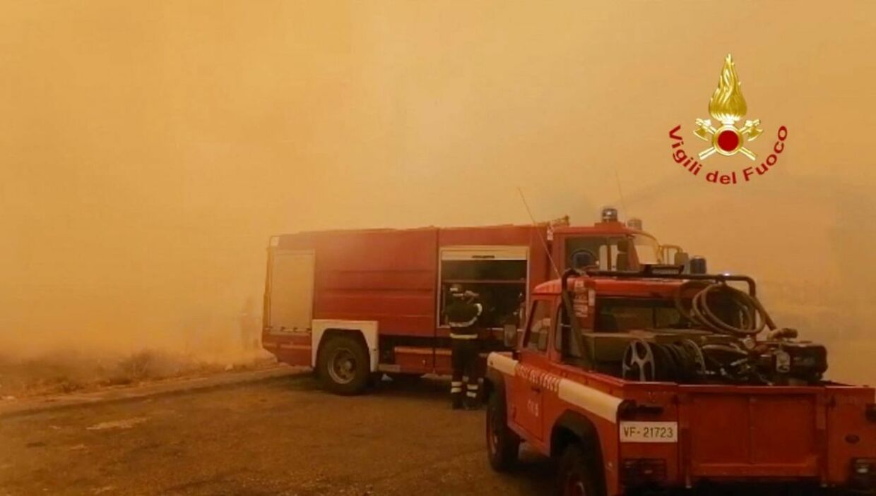 """A picture taken and released on July 25, 2021 by the Italian Firefighters """"Vigili del Fuoco"""" shows fire crews near the sits of a fire burning actively around the town of Oristano, on Sardinia island. - Firefighting aircraft from France and Greece arrived in Italy on July 25, 2021 following an appeal for help in taming fires raging across parts of Sardinia that have forced hundreds of people from their homes. (Photo by Handout / Vigili del Fuoco / AFP) / RESTRICTED TO EDITORIAL USE - MANDATORY CREDIT """"AFP PHOTO / VIGILI DEL FUOCO - ITALIAN FIRE FIGHTERS"""" - NO MARKETING NO ADVERTISING CAMPAIGNS - DISTRIBUTED AS A SERVICE TO CLIENTS"""
