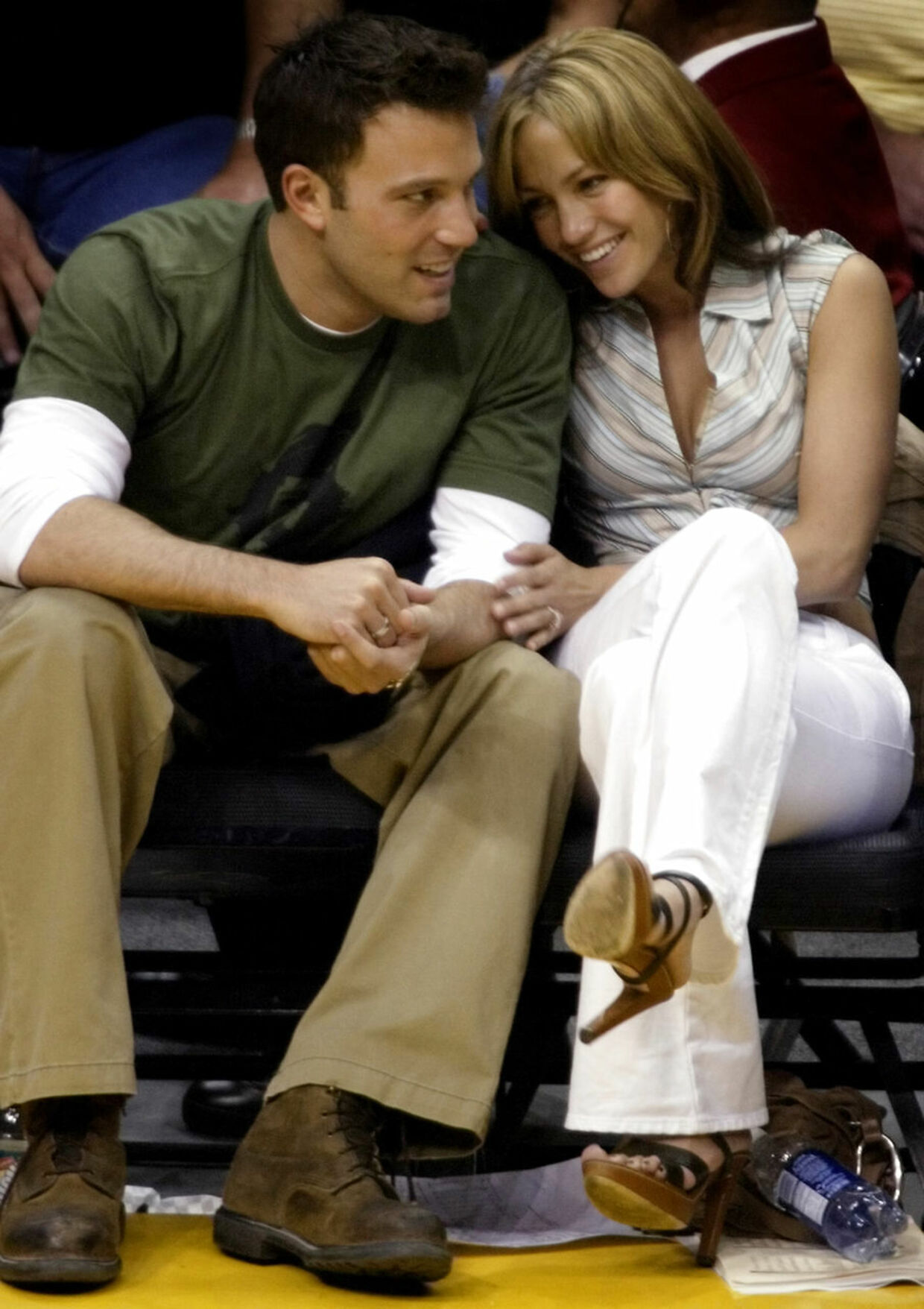 Hollywood couple Ben Affleck gets a smile from fiancee Jennifer Lopez during the Los Angeles Lakers San Antonio Spurs NBA Western Conference semifinal in Los Angeles May 11, 2003. The two actors enjoyed the game court side as the Lakers defeated the Spurs 99-85 to tie their best-of-seven series at 2-2. REUTERS/Mike Blake