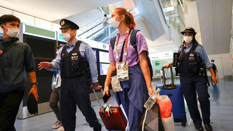 Krystsina Tsimanouskaya bliver her eskorteret af politiet i lufthavnen.