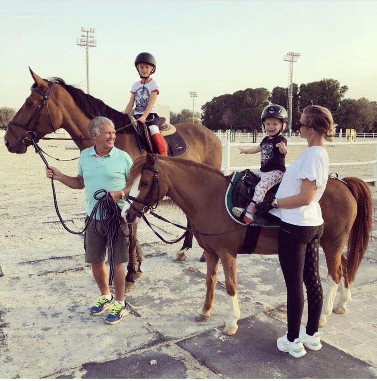 Tina Lund med sine børn og sin far, der altid har været meget engageret i hendes ridekarriere.