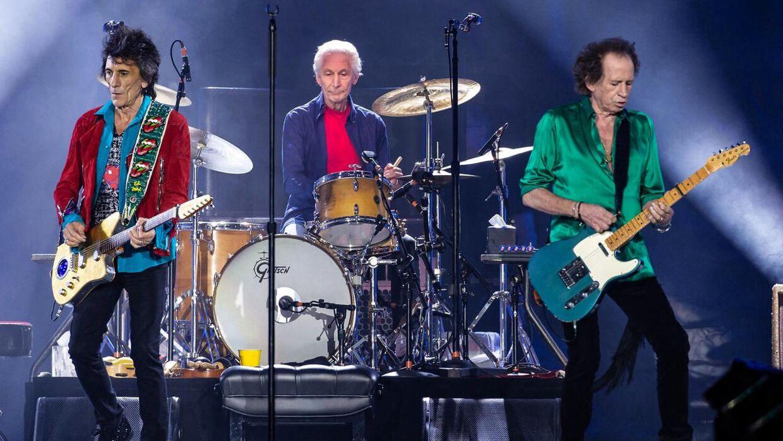 Charlie Watts, hvor han nærmest altid var, mellem de øvrige medlemmer af The Rolling Stones. Her er det mellem Ronnie Woods og Keith Richards på scenen i 2019.