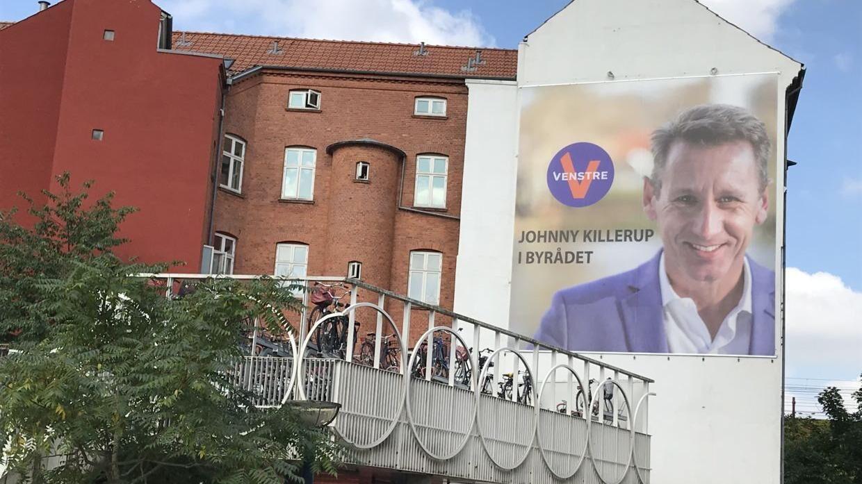Johnny Killerups plakat for venstre hænger stadig ved Odense Banegårdscenter.