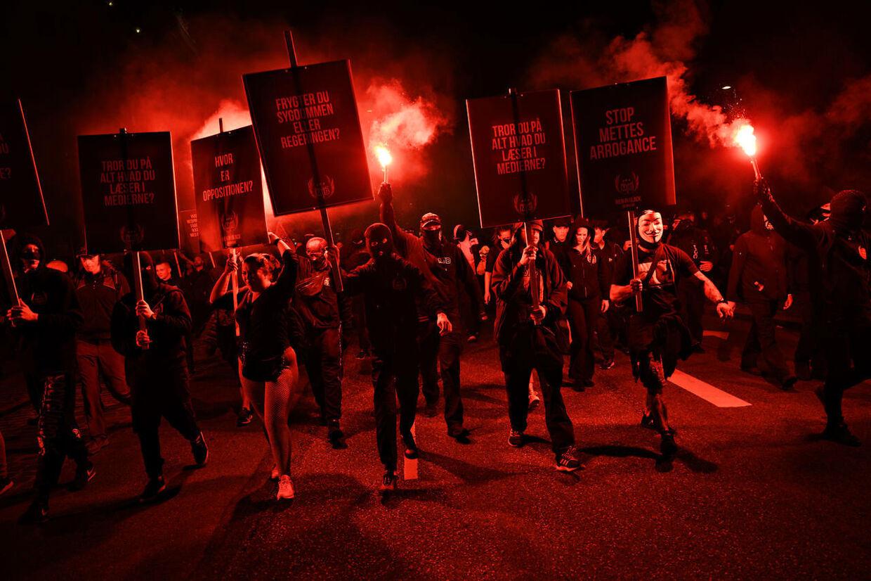 Sortklædte demonstranter med nødblus til Men in Black-demonstration i København.