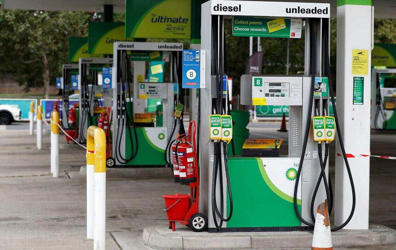 Der hænger skilte med 'ude af drift' ved pumperne på en tankstation, der er løbet tør for brændstof.