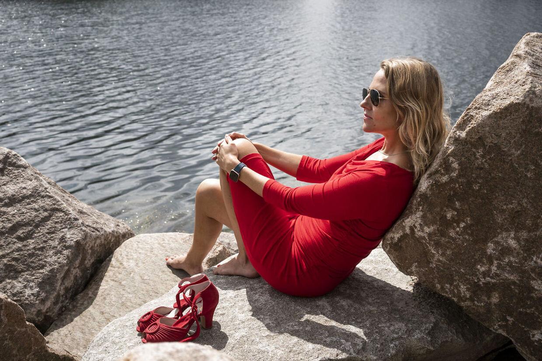 Radiovært og feminist Christiane Vejlø – her fotograferet siddende iført kropsnær rød sommerkjole med tilhørende højhælede røde sko – er vred over, at en journalist har beskrevet Inger Støjbergs udseende i en reportage fra Rigsretten.