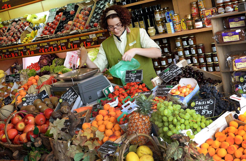 En sælger holder en plastikpose, mens hun pakker kartofler på et frugt og grøntmarked i Paris den 13. juni 2014.