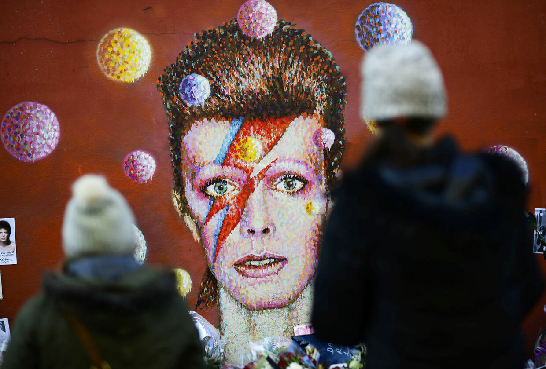 På billedet ses David Bowies legendariske figur Ziggy Stardust portrætteret. Foran maleriet af rocklegenden står to fans og tager afsked. Kort før hans død udgav David Bowie sit sidste album med titlen 'Blackstar'.