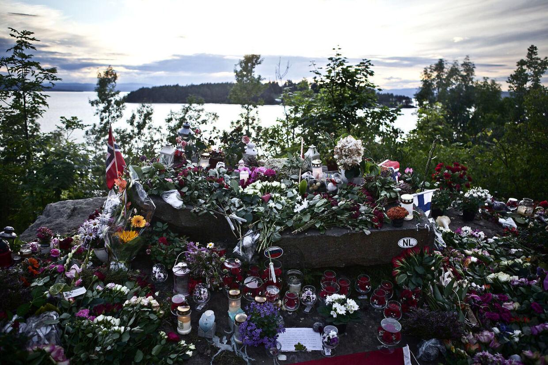 En bunke lys og roser ligger i bunker og i baggrunden ses Utøya.