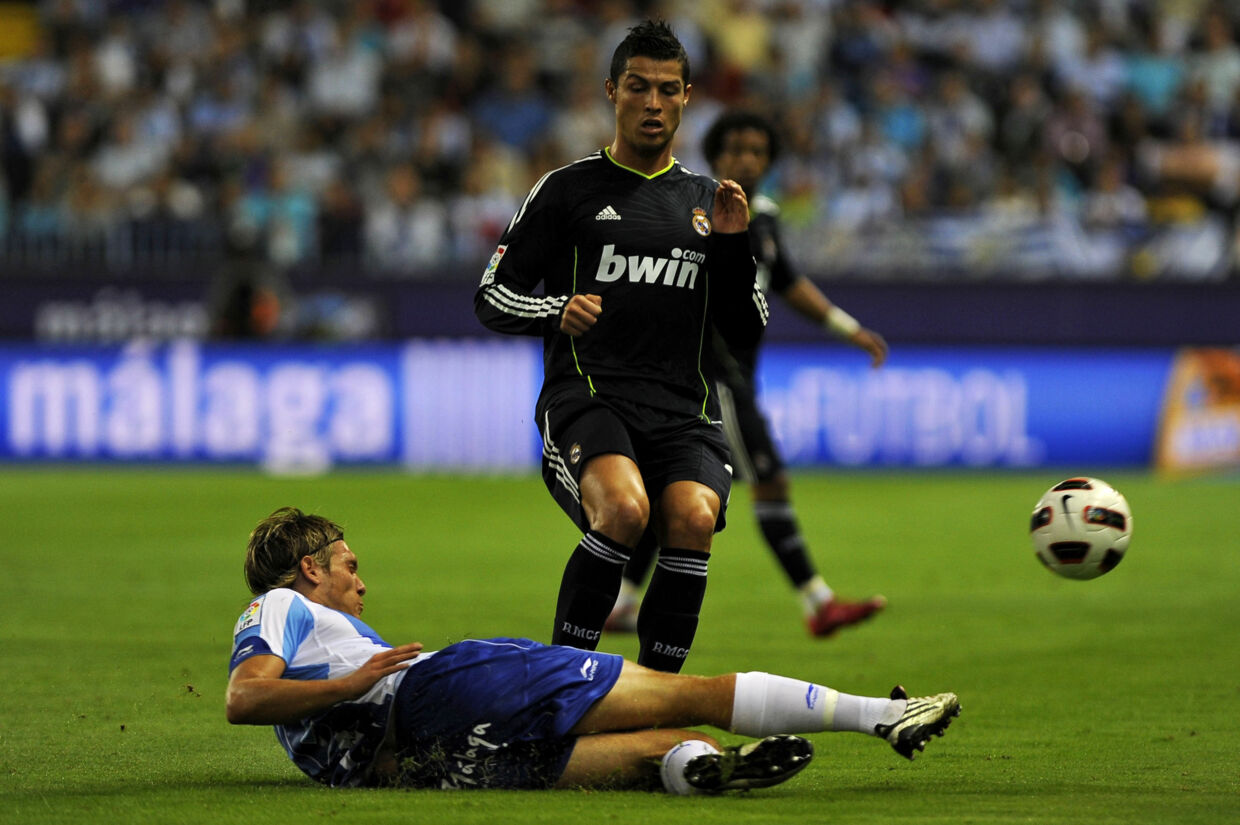 Real Madrid's Portuguese forward Cristiano Ronaldo (Top) vies for the ball with Malaga's Danish defender Kris Stadsgaard during their Spanish league football match Malaga against Real Madrid at Rosaleda stadium on October 16, 2010 in Malaga. AFP PHOTO/ JORGE GUERRERO