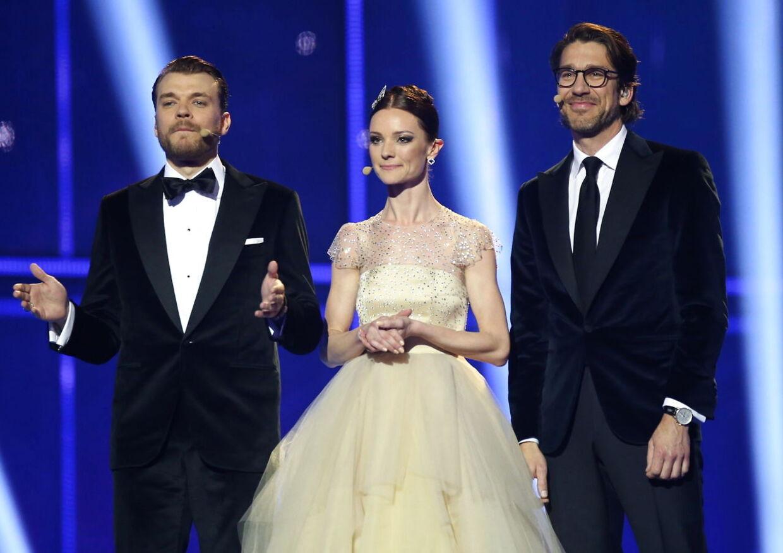 Pilou Asbæk, Lise Rønne og Nikolaj Koppel var værter for Det internationale Melodi Grand Prix, der blev sendt fra København i maj 2014. Grandprix'et blev en dyr fornøjelse, skulle det senere vise sig.