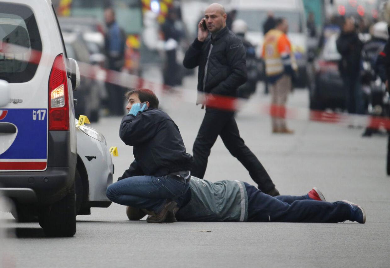 Politiet arbejder her nær redaktionen for satiremagasinet Charlie Hebdo onsdag. Herhjemme er en 23-årig blevet sigtet af Københavns Politi for at glæde sig over terror-anslaget.