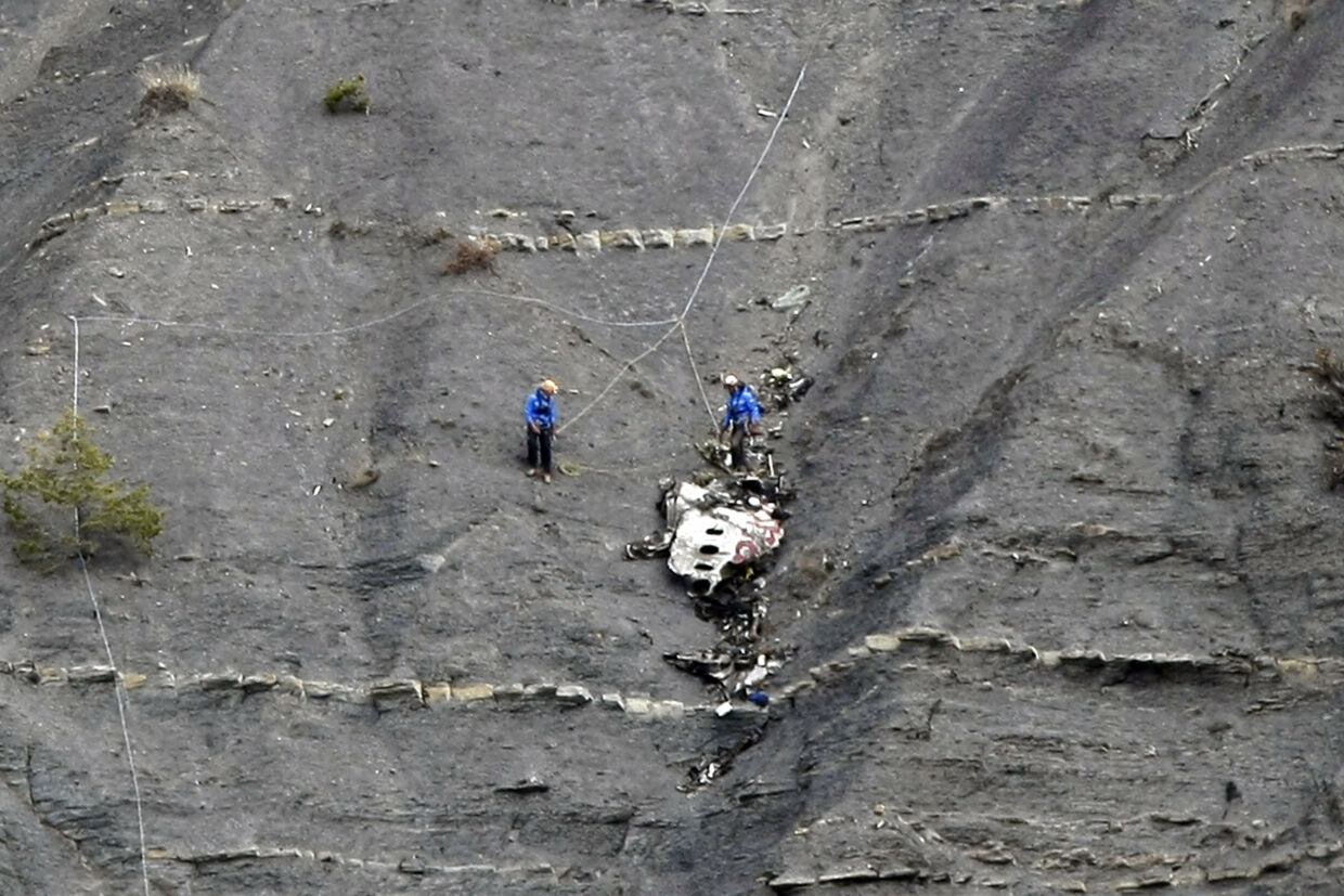 Rescue workers are seen near debris at the crash site of the Germanwings Airbus A320 near Seyne-les-Alpes, French Alps, March 30, 2015. The young German co-pilot, Andreas Lubitz, suspected of deliberately crashing a passenger plane in the French Alps, killing all 150 people on board including himself, told his girlfriend he was in psychiatric treatment, and that he was planning a spectacular gesture that everyone would remember, the German daily Bild reported on Saturday. REUTERS/Claude Paris/Pool
