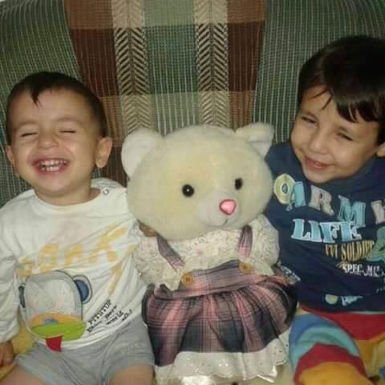 Aylan på tre år og hans storebror, Galip, på fem år ses her smilende sammen med en tøjbamse. Onsdag morgen blev de fundet druknet, da deres båd på vej mod den græske ø Kos kæntrede.