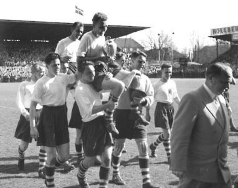 """Pokalfinale i fodbold, AGF - Esbjerg (2 - 0). """"AGF vandt pokalen"""", skriver Berlingske Tidende mandag den 29. april 1957. """"Skønt aarets fodboldfinale i DBUs landspokalturnering i København blev spillet mellem to jyske hold, var der dog næsten 26.000 tilskuere i Idrætsparken i gaar. De fik en spændende kamp at se, som AGF vandt 2 - paa maal scoret i de sidste minutter"""". Her bæres AGFs anfører Aage Rou Jensen i guldstol med pokalen efter den haarde dyst""""."""