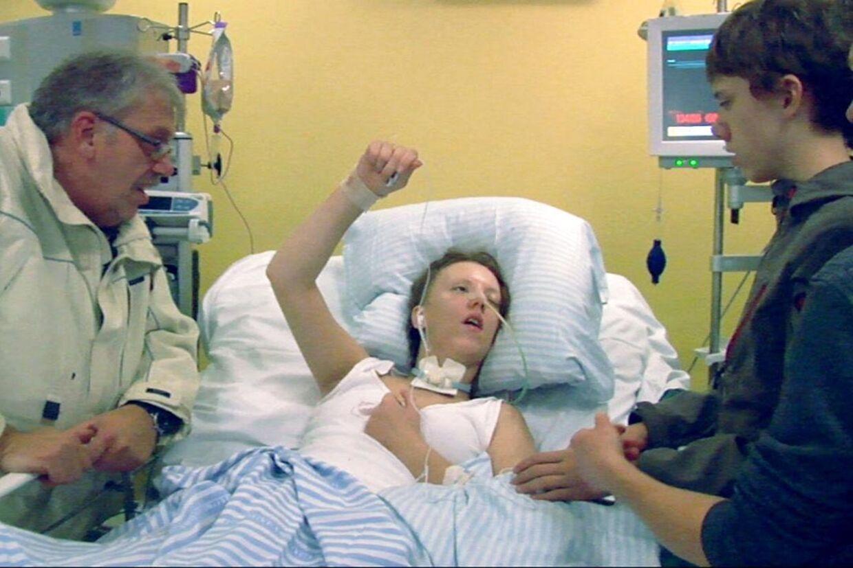 Carinas forældre og bror i en stille, alvorlig stund sammen med den hjerneskadede pige på hospitalet i Aarhus.