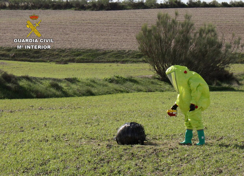 En sikkerhedsmedarbejder inspicerer en metalgenstand, som den 4. november 2015 landede på en mark i den sydøstlige Spanien. På blot én uge, er der faldet tre mystiske genstande ned fra rummet i det spanske område. Foto: AFP