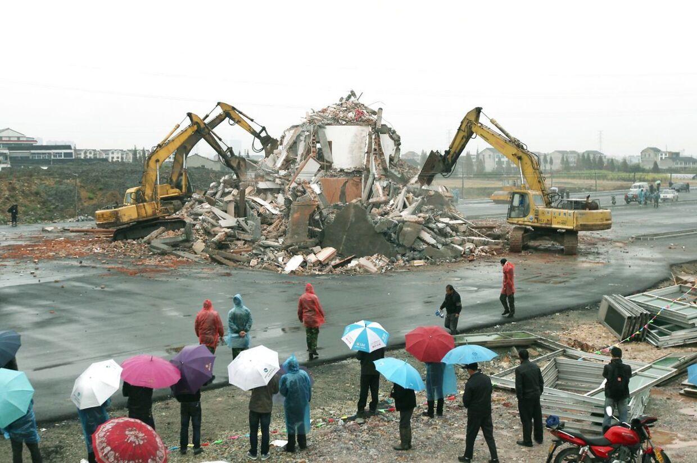 Huset midt på den nybyggede kinesiske motorvej er fortid. Gravkøer og bulldozere jævnede det med jorden i lørdags efter, at ejerne havde accepteret en kompensation på 40.000 dollars.
