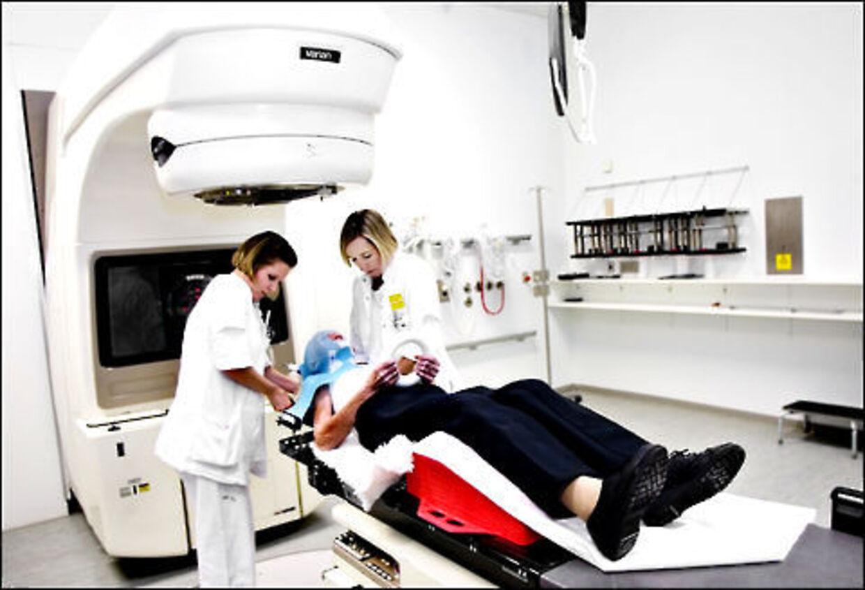 Lisbeth Rodian og Margit Engberg (th.) gør en patient klar til strålebehandling på Rigshospitalet.