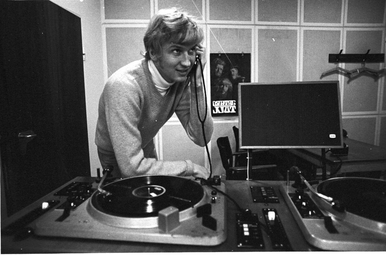 Sådan så han ud dengang, dagens jubilar. Jørgen Mylius, programmedarbejder, Danmarks Radio lyder billedteksten på dette foto fra vores arkiv. Jørgen de Mylius fotograferet ved pladespillerne i DR-studiet for næsten 50 år siden.