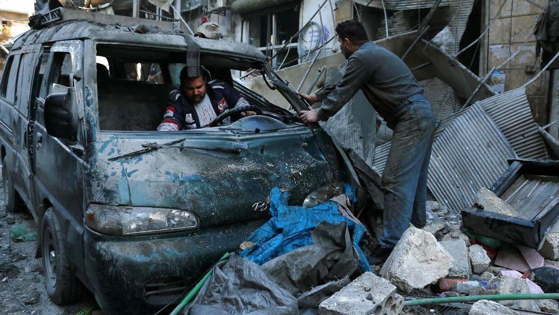 Mænd ser på en beskadiget bil efter et blodigt angreb fra Islamisk Stat i byen Deir Ezzor.