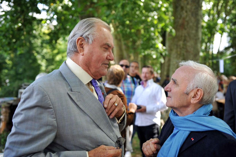 Den 88-årige sanger Charles Aznavour (th), som her ses i samtalemed prins Henrik under en litteraturfestival i Frankrig sidste år, ejer det store franske musikforlag Raoul Breton.