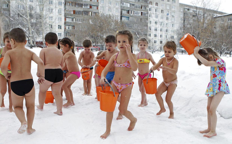 En flok børnehavebørn leger med vand i den russiske by Barnaul, selvom termometeret viser minus 25 grader.