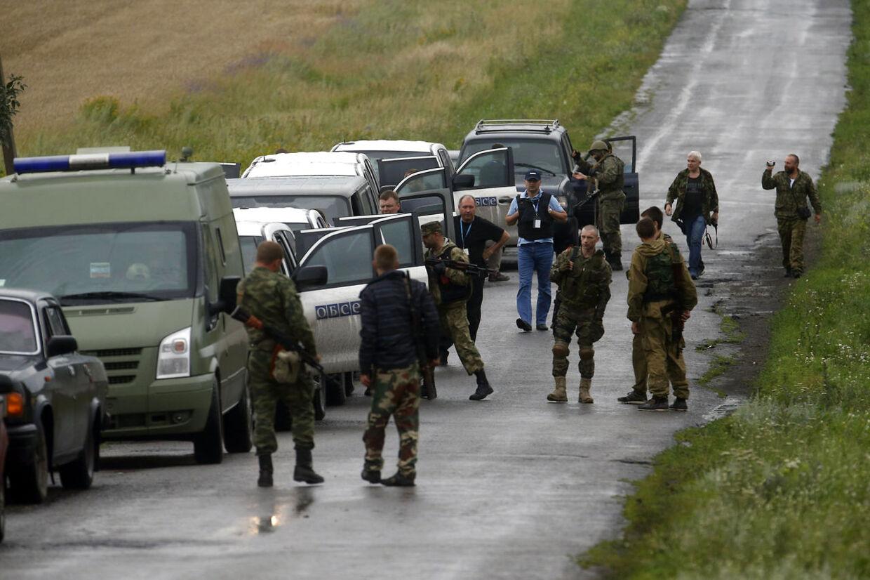 Flere internationale medier har fredag aften berettet, at prorussiske oprørere åbnede ild mod OSCE-observatørerne, da de nærmede sig flyvraget, men den oplysning kan Thomas Greminger hverken be- eller afkræfte. Observertørerne blev i hvert fald mødt af bevæbnede mænd, da de ankom til ulykkesstedet, som dette billede viser.
