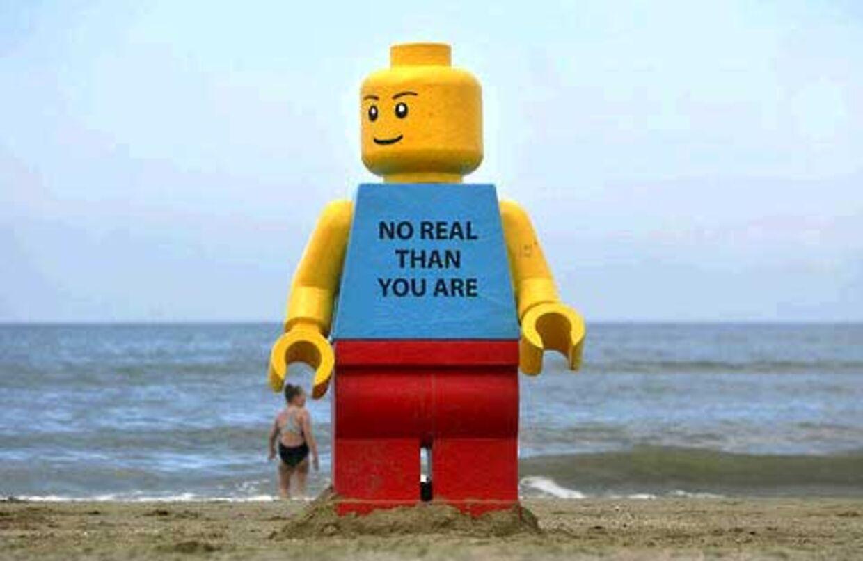 Legomanden står troligt, med fødderne nedgravet i sandet, på stranden i Holland.