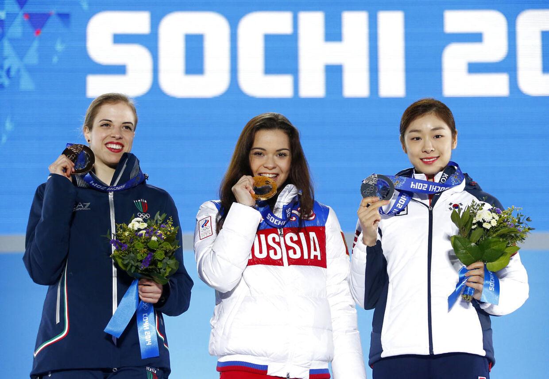 Russiske Adelina Sotnikova (i midten) vandt guld i kvindernes kunstskøjteløb, ogYuna Kim fra Sydkorea (til højre) vandt sølv, men mange mener, det burde have været omvendt og kræver nu, at kvindernes præsationer bedømmes på ny.