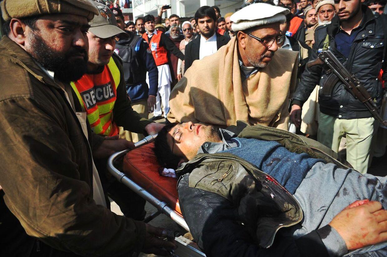 En såret mand bliver båret på hospitalet efter angrebet i Pakistan.