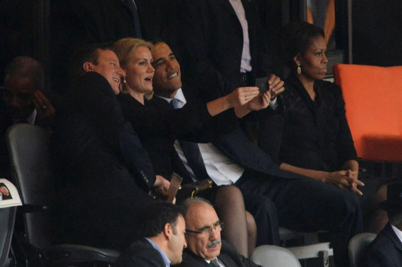 Helle Thorning tager et billede af sig selv sammen med to af verdens mest mægtige mænd, den amerikanske præsident Barack Obama (th) og den britiske premierminister, David Cameron, til mindehøjtideligheden for Nelson Mandela i Sydafrika. Længst til højre ses den amerikanske førstedame, Michelle Obama.