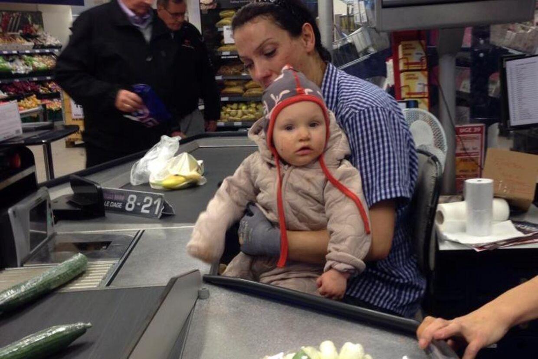 Her sidder kassedamen med Sarah Ulbrichsens 11 måneder gamle datter på skødet. Tårerne kan stadig ses på kinderne.