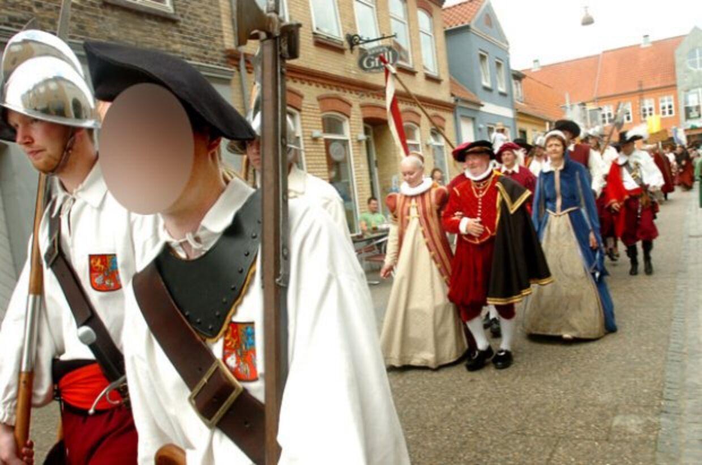 Den 25-årige tiltalteses her (masket ansigt) under et optog iklædt middelaldertøj.