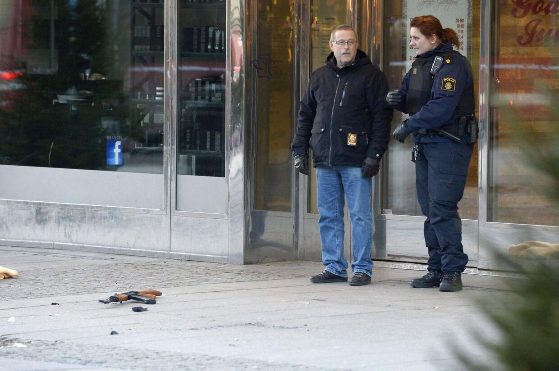 Her står politifolk ved røvernes efterladt Kalashnikov-riffel ved guldsmedeforretningen i Södertälje, 50 kilometer syd for Stockholm.