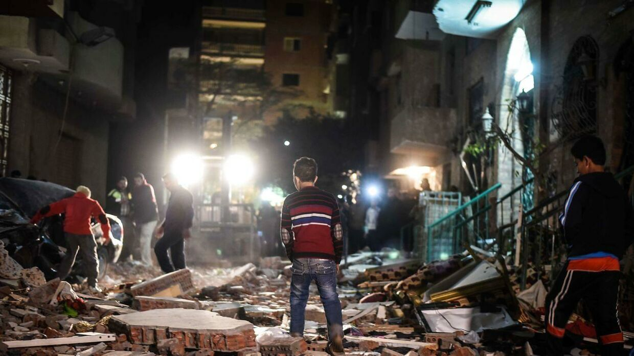 Egyptians stand guard at the scene of a bomb blast in a main street in Giza on January 21, 2016. A bomb attack killed six people, including three policemen, on Thursday near a road leading to the pyramids in the Cairo suburb of Giza, security sources said. / AFP / MOHAMED EL-SHAHED / MOY