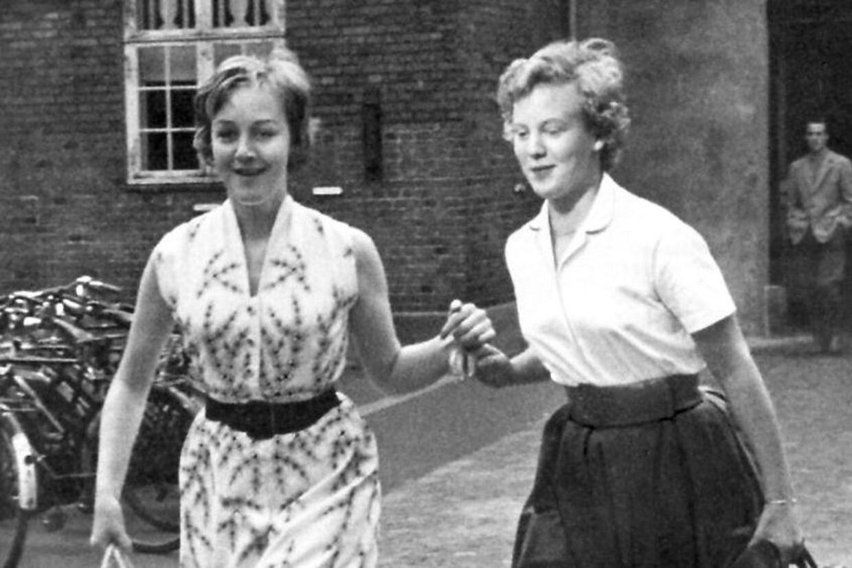 Dronning Margrethemed Helle Stangerup i hånden på vej til deres første forelæsning i statsforfatningsret på Københavns Universitet i 1959. De to studiner ankom så sent til auditoriet, at alle pladser var optaget, og demåtte stå op, indtil de fik tilbudt siddepladser bagest i salen.