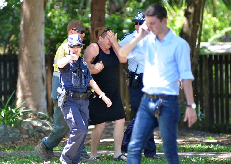 En ukendt kvinde modtager trøst af politiet efter et uhyggeligt ottedobbelt knivdrab i forstaden Manoora i Cairns, Australien.
