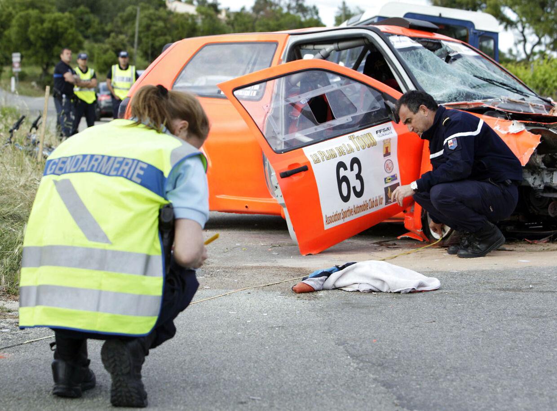 En fransk politimand arbejder ved ulykkesbilen, der dræbte to under et rally i Sydfrankrig.