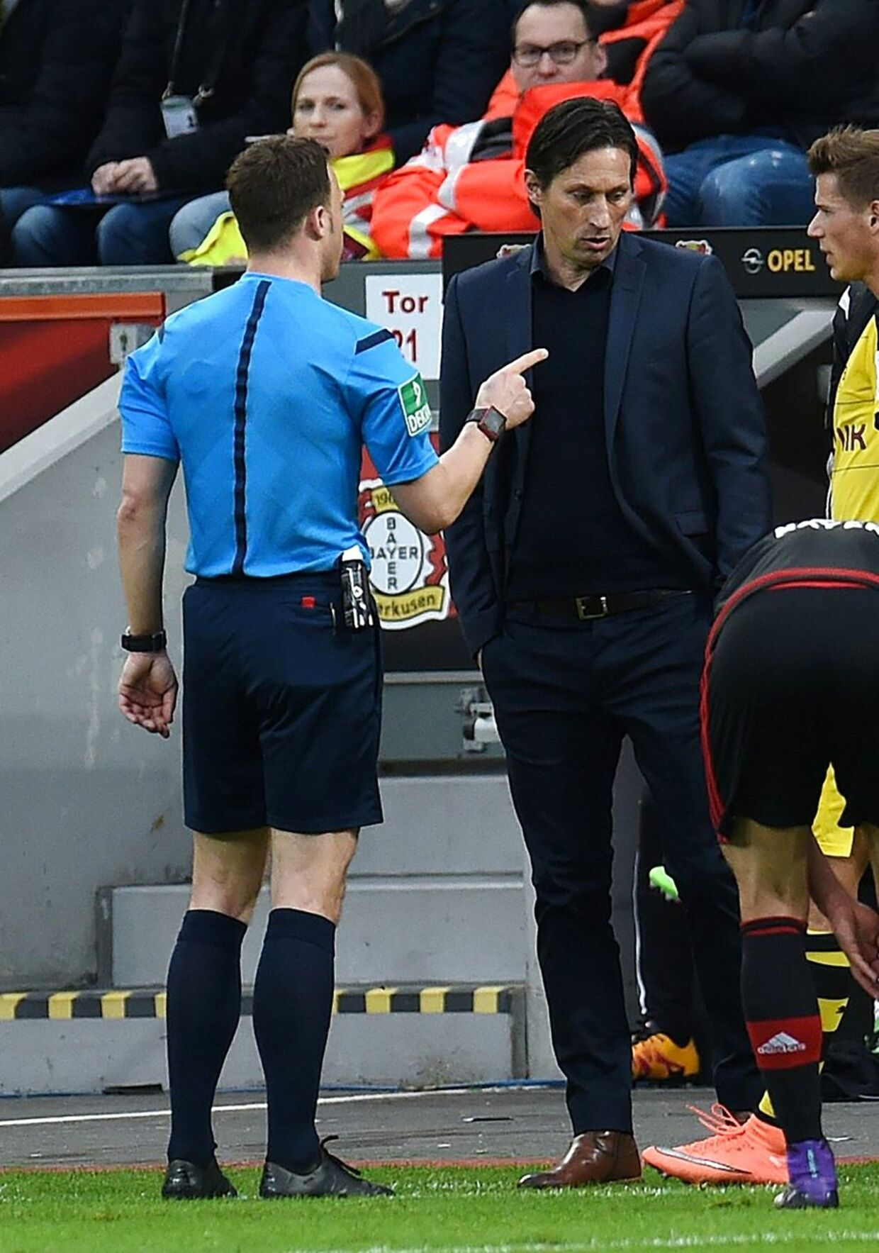 Referee Felix Zwayer (L) talks to Leverkusen's head coach Roger Schmidt during the German first division Bundesliga football match of Bayer 04 Leverkusen vs Borussia Dortmund in Leverkusen, western Germany, on February 21, 2016. / AFP / PATRIK STOLLARZ / RESTRICTIONS: DURING MATCH TIME: DFL RULES TO LIMIT THE ONLINE USAGE TO 15 PICTURES PER MATCH AND FORBID IMAGE SEQUENCES TO SIMULATE VIDEO. == RESTRICTED TO EDITORIAL USE == FOR FURTHER QUERIES PLEASE CONTACT DFL DIRECTLY AT + 49 69 650050