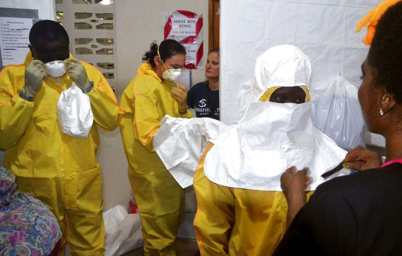 Læger og sygeplejersker ifører sig beskyttelsesdragter på ELWA-hospital i Liberias hovedstad Monrovia. Ebola-epidemien har nu fået præsidenten Afrikas mest folkerige nation, Nigeria, til at erklære landet i undtagelsestilstand.