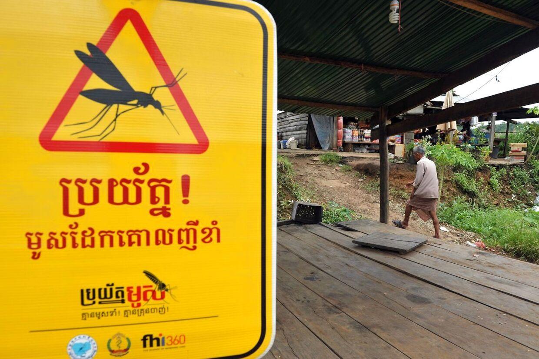 Et skilt advarer indbyggerne i en cambodjansk landsby mod faren for maliariamyg.