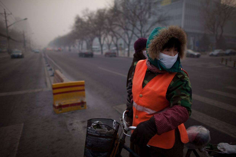En cyklist bærer en maske, mens hun cykler igennem den forurenede Beijing-