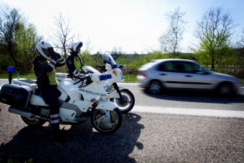 PARAT: Mens to politifolk på en bro måler farten på bilisterne, holder fire motorcykler og to biler klar til at sætte efter synderne. Motorcyklerne er hurtige nok til at fange selv den hurtigste fartbilist. Foto: Peter Clausen