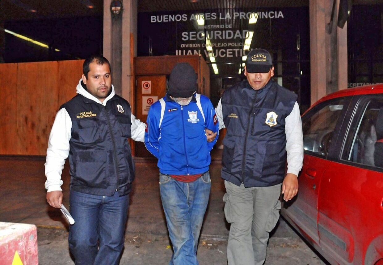 Her bliver den 66-årige Eduardo Oviedo ført væk af to politimænd.