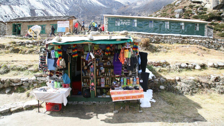 Langt inde i Hinku-dlane, i »byen« Tangnag, kan man kan man købe en souvenir eller en uldhue. I baggrunden tehuset – med værelser i bygningen til højre og fællesrum til venstre. Foto: Søren Norman Pedersen