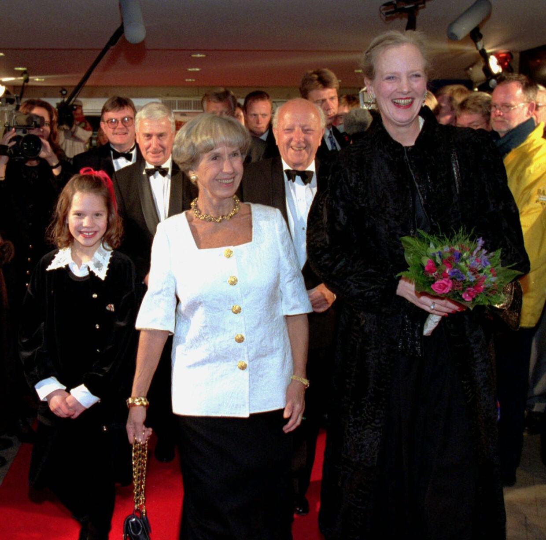 Dronning Margrethe til galla-premiere på filmen 'Kun en pige' i 1995. Dronningen blev budt velkommen af forfatteren Lise Nørgaard, der har skrevet bogen bag filmen. Til venstre ses en ung Amalie Dollerup, som spillede Lise Nørgaard som barn i filmen. Foto: Nordfoto
