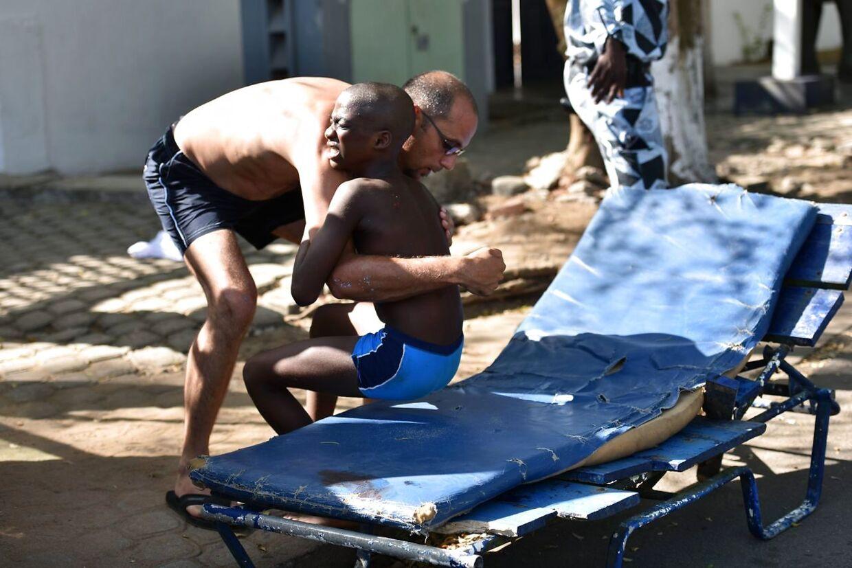 En mand hjælper en såret dreng efter skudangrebet på stranden i Grand-Bassam.